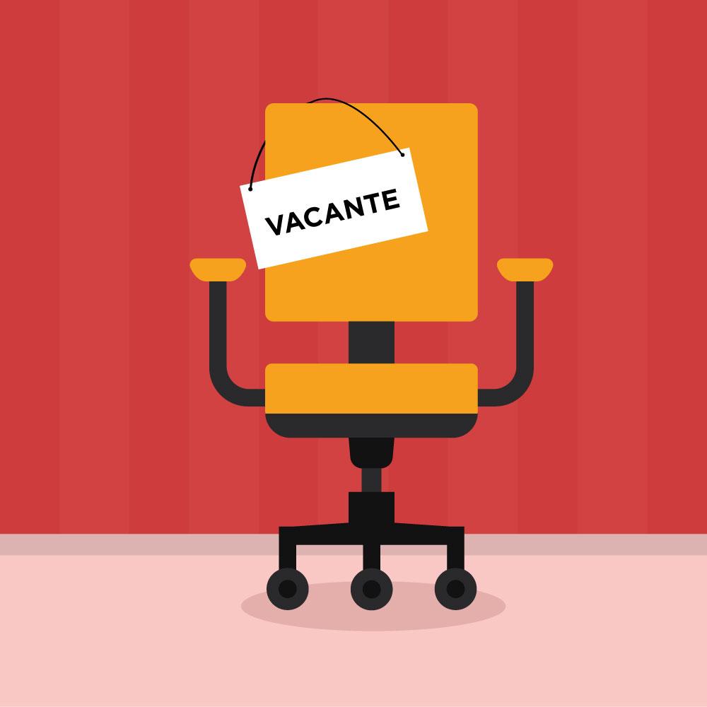 """Una silla de oficina color amarillo al centro, con un letrero que cuelga del respaldo de la misma que dice: """"VACANTE""""."""