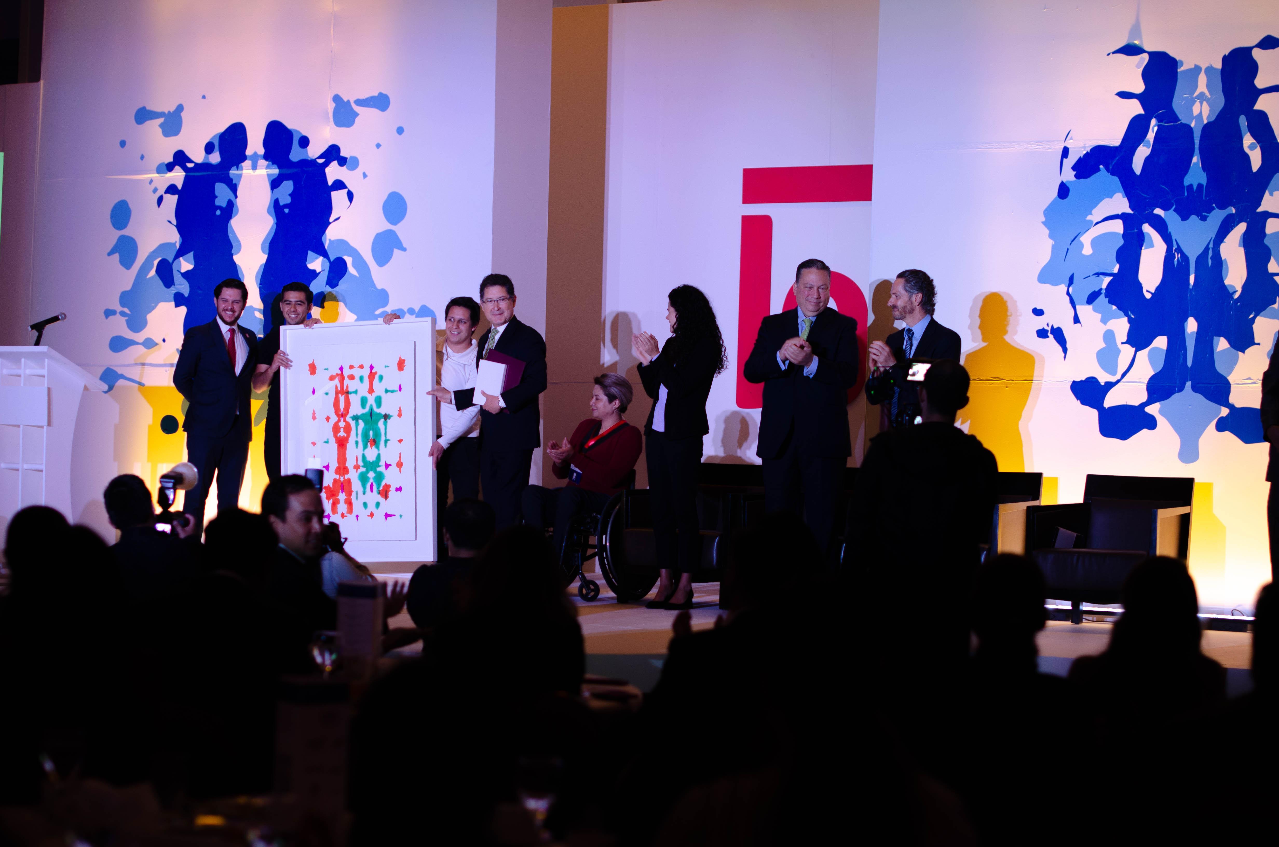 Fernando Estrada, Director de Éntrale, entrega un cuadro a Lala por ser ganador del Premio Éntrale