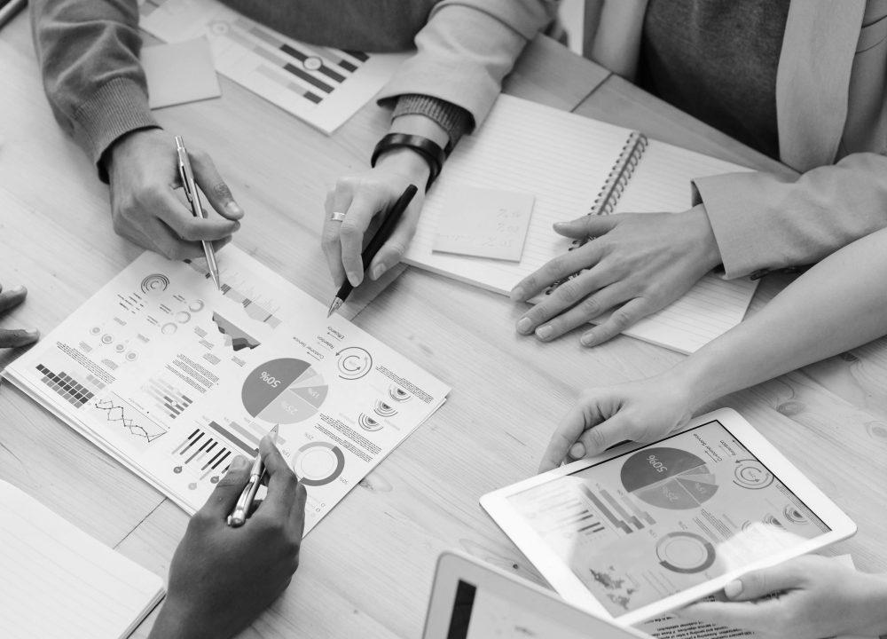 Mesa de juntas con documentos, estadísticas, y personas señalando los datos